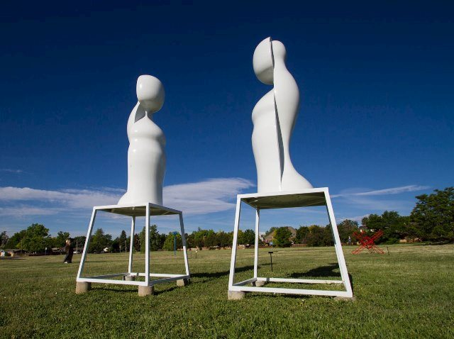 Two white sculptures shaped like abstract figures in our sculpture field