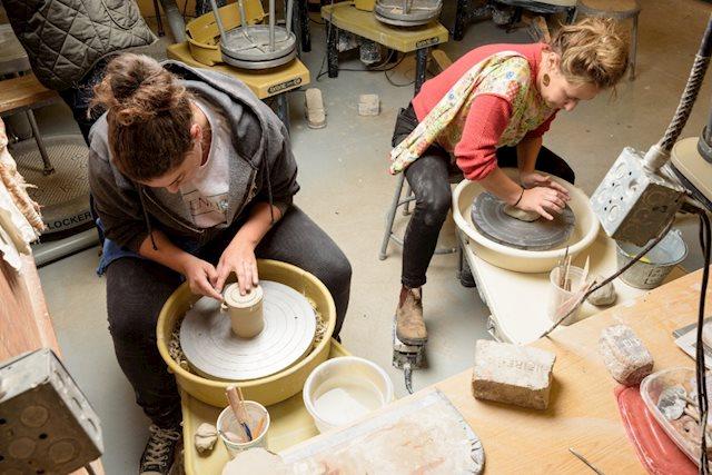 Two women work on pottery wheels